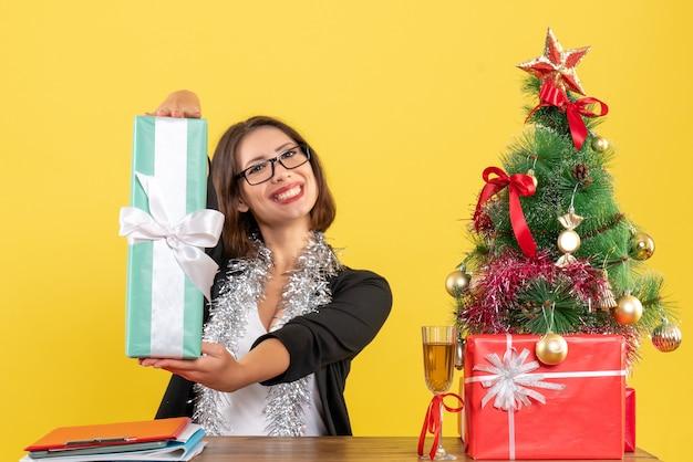 Uśmiechający się biznes dama w garniturze z okularami pokazujący jej prezent i siedząc przy stole z drzewem xsmas na nim w biurze