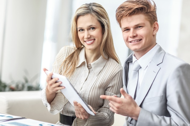 Uśmiechający się biznes para patrząc na ekranie cyfrowego tabletu.