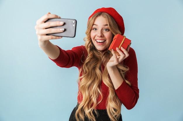 Uśmiechający się blond kobieta lat 20-tych trzymając pudełko urodzinowe podczas robienia zdjęcia selfie na telefon komórkowy na białym tle