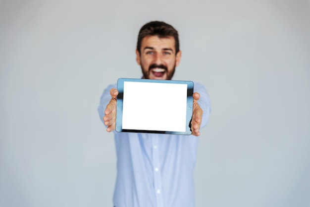 Uśmiechający się brodaty biznesmen stojący przed białym tle i trzymając tabletkę