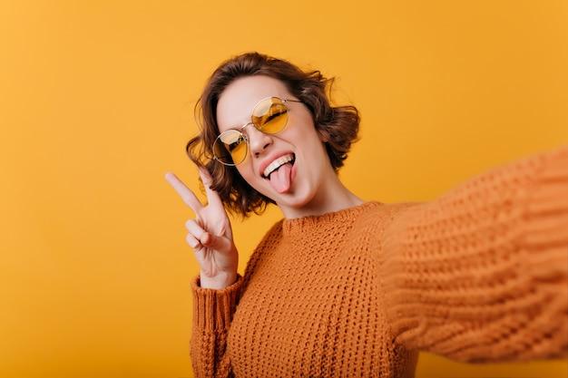 Uśmiechający się brunet dziewczyna pozuje z języka. szczegół portret uroczej ładnej pani w dobrym nastroju, dzięki czemu selfie na jasnej ścianie.