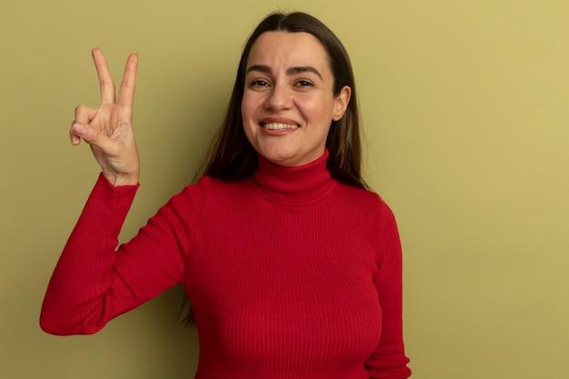 Uśmiechający się całkiem kaukaski kobieta gestykuluje ręką znak zwycięstwa na oliwkowej zieleni