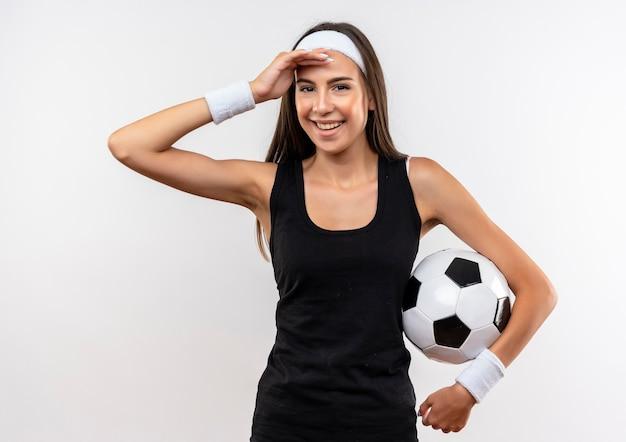 Uśmiechający się całkiem sportowy dziewczyna na sobie opaskę i opaskę, trzymając piłkę nożną i kładąc rękę na czole na białym tle na białej przestrzeni