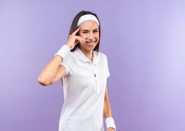 Uśmiechający się całkiem sportowy dziewczyna nosi opaskę i opaskę kładąc palec na świątyni na białym tle na fioletowej przestrzeni