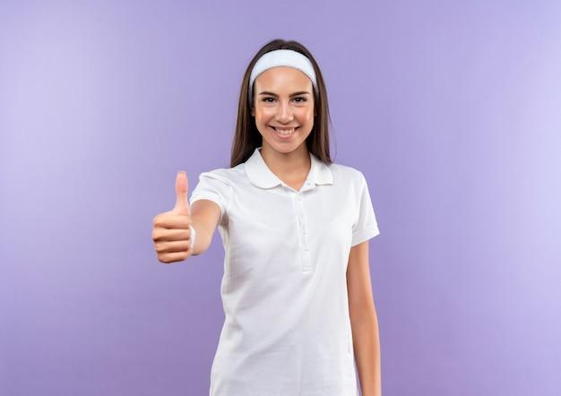 Uśmiechający się całkiem sportowy dziewczyna nosi opaskę i opaskę pokazując kciuk do góry na białym tle na fioletowej przestrzeni