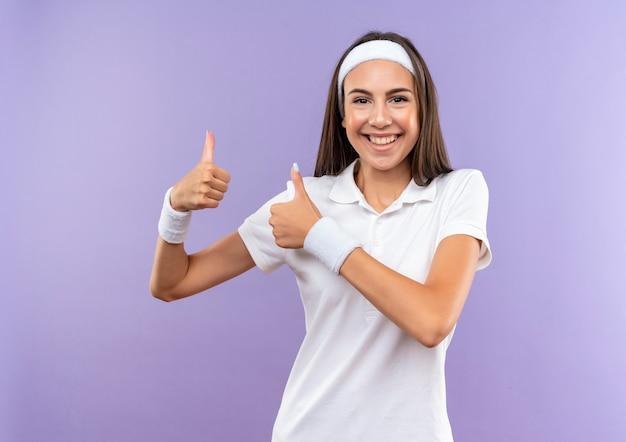 Uśmiechający się całkiem sportowy dziewczyna nosi opaskę i opaskę pokazując kciuki do góry na białym tle na fioletowej przestrzeni