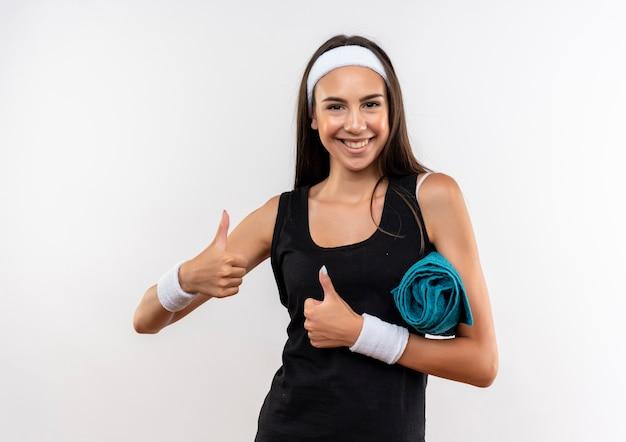 Uśmiechający się całkiem sportowy dziewczyna nosi opaskę na głowę i opaskę trzymając ręcznik pokazując kciuki do góry na białym tle na białej przestrzeni