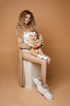 Uśmiechający się długowłosy stylowa dama siedzi z rozbawionym maluchem dziewczyna na kolanach. na białym tle na beżowym tle