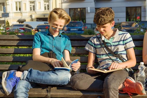 Uśmiechający się dwóch szkolnych chłopiec czyta książki siedzi na ławce w mieście