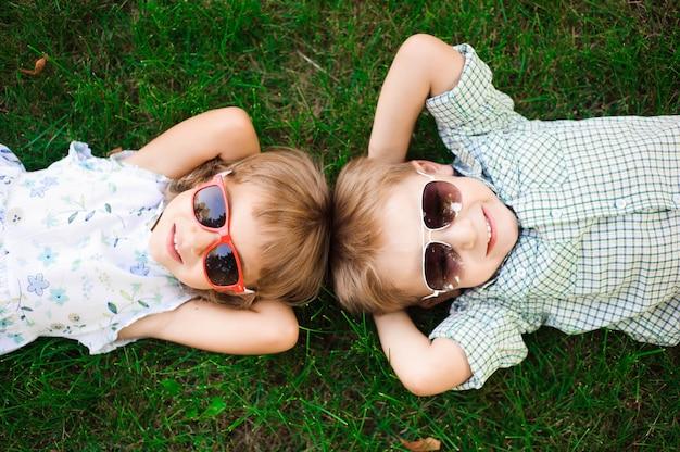 Uśmiechający się dzieci w ogrodzie w okulary