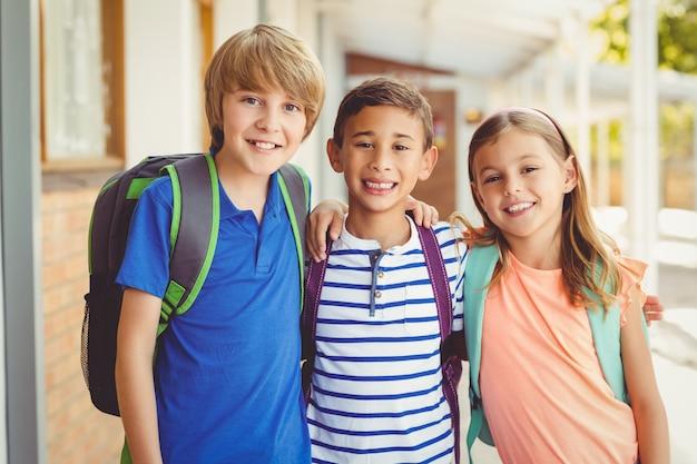 Uśmiechający się dzieci w szkole stojącej w szkolnym korytarzu z ramieniem wokół