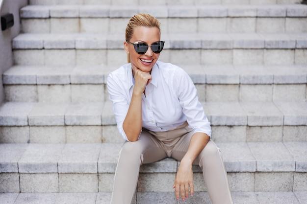 Uśmiechający się efektowne atrakcyjne modne blond kobieta z ręką na brodzie, siedząc na zewnątrz na schodach.