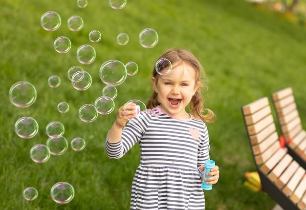 Uśmiechający się emocjonalny roześmiany wyraz dziecko dziewczynka dmuchanie baniek zupy w letniej przyrodzie. świeże zielone tło trawy. latające baniek mydlanych. zajęcia na świeżym powietrzu, letnie wakacje z dziećmi.