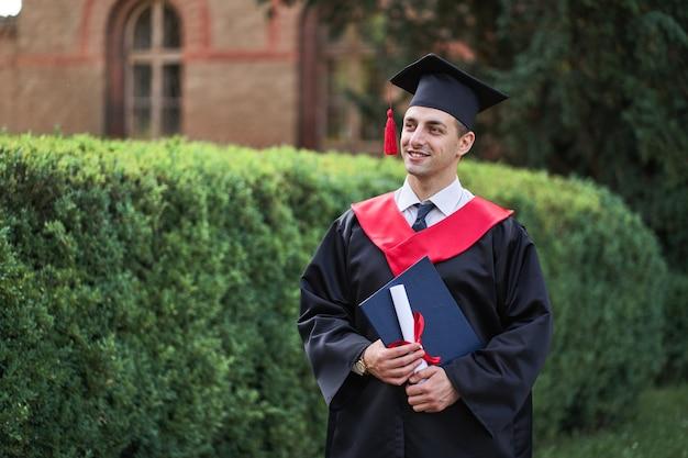 Uśmiechający się kaukaski absolwent płci męskiej w szacie ukończenia szkoły z iploma.