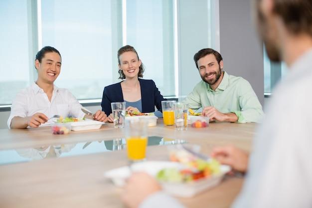 Uśmiechający się kierownictwo firmy o posiłek w biurze