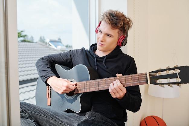 Uśmiechający się kreatywny nastolatek w słuchawkach siedzi na parapecie i gra na gitarze