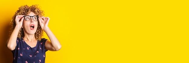 Uśmiechający się kręcone włosy młoda kobieta w przezroczystych okularach na żółtym tle.