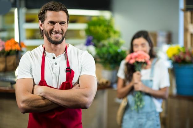 Uśmiechający się kwiaciarnia stojąca w kwiaciarni z rękami skrzyżowanymi