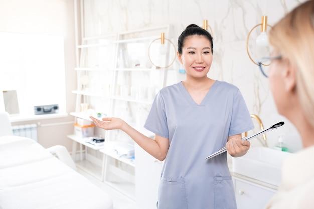 Uśmiechający się ładny kosmetolog w zarośla trzymając schowek i powitanie klienta w gabinecie kosmetycznym