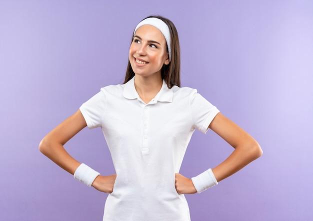 Uśmiechający się ładny sportowy dziewczyna ubrana w opaskę i opaskę z rękami w talii patrząc na bok na białym tle na fioletowej przestrzeni