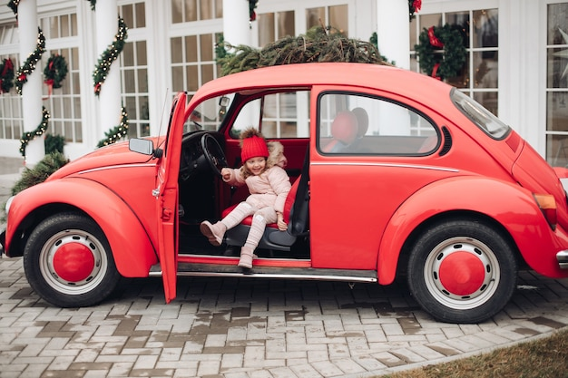 Uśmiechający się ładny zima dziewczyna w czerwonym kapeluszu siedzi w samochodzie zabawy średni strzał. szczęśliwe piękne kobiece dziecko w ciepłej odzieży, mające pozytywne emocje na świeżym powietrzu, otoczone płatkami śniegu cieszące się dzieciństwem