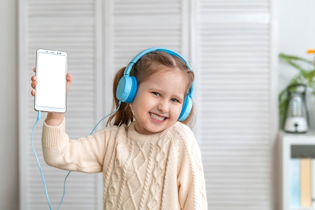 Uśmiechający się małe dziecko dziewczynka w słuchawkach pokazuje biały pusty ekran