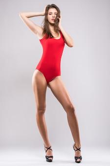 Uśmiechający się malutki model dziewczyna w czerwonym zestawie kąpielowym na białym tle