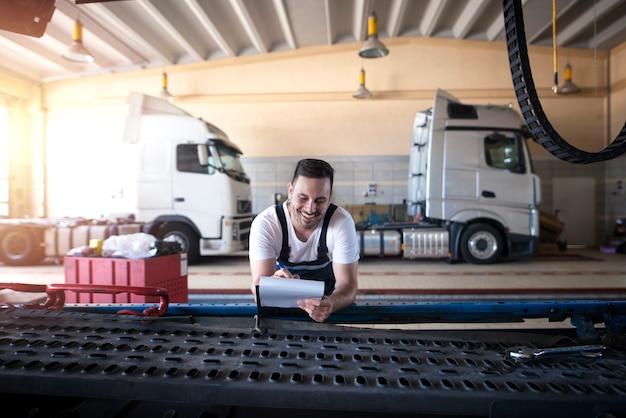 Uśmiechający się mechanicy ciężarówek wykonujący papierkową robotę przed serwisem pojazdu w warsztacie samochodowym.