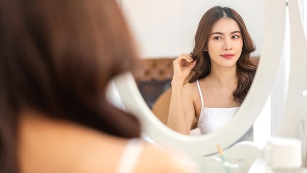 Uśmiechający się młoda piękna ładna azjatykcia kobieta czysta świeżą, zdrową białą skórę patrząc w lustro. azjatycka dziewczyna dotyka jej twarzy ręką i nakłada krem w domu.
