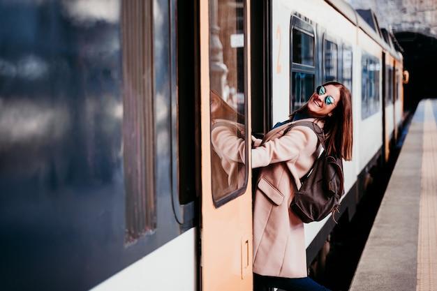 Uśmiechający się młody backpacker kaukaski kobieta stojąc na wagonie na stacji kolejowej. koncepcja podróży