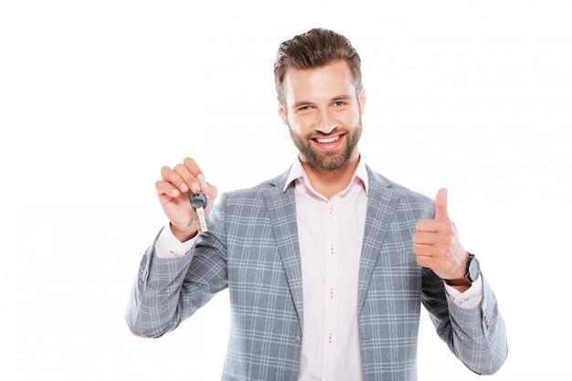 Uśmiechający się młody człowiek trzyma klucze