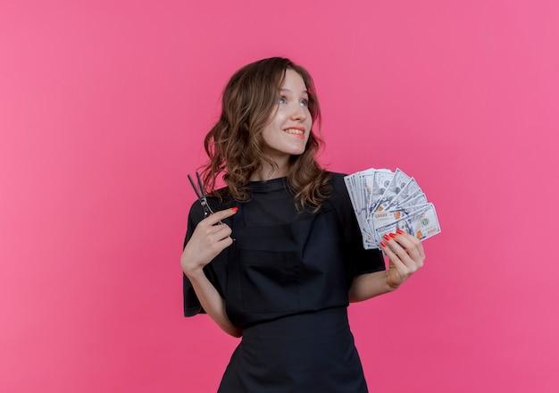 Uśmiechający się młody słowiański fryzjer w mundurze patrząc na boczne gryzące wargi, trzymając pieniądze i nożyczki na białym tle na różowym tle z miejsca na kopię