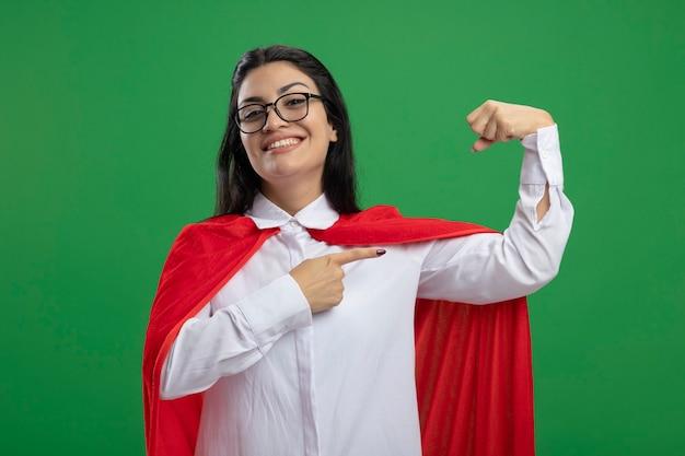 Uśmiechający się młody superbohater kaukaski dziewczyna w okularach zginając jej mięśnie i zaczyna się bawić patrząc na kamery na białym tle na zielonym tle