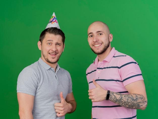 Uśmiechający się młodzi imprezowicze, jeden w czapce urodzinowej, obaj pokazujący kciuki do góry na białym tle na zielono