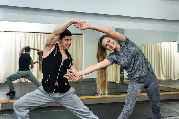 Uśmiechający się młodzi ludzie ćwiczeń na siłowni