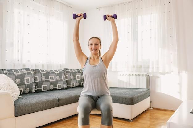 Uśmiechający się muskularny sportsmenka siedzi na krześle w swoim mieszkaniu i robi ćwiczenia fitness na biceps z hantlami.