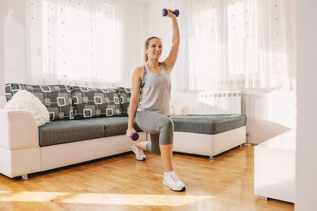 Uśmiechający się muskularny sportsmenka w kształcie robi rzuty trzymając hantle.