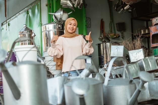 Uśmiechający się muzułmańska kobieta stoi z kciukami w sklepie agd