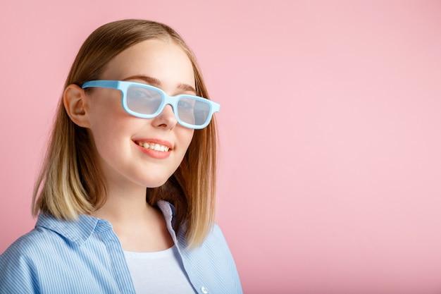 Uśmiechający się nastolatek dziewczyna portret widza filmu w okularach na białym tle różowy kolor ściany z miejsca kopiowania. młoda kobieta w okularach kinowych do oglądania filmów 3d w kinie.