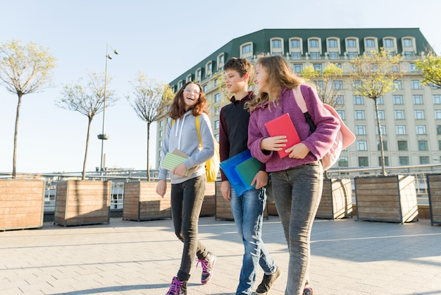 Uśmiechający się nastolatki z plecakami i podręcznikami