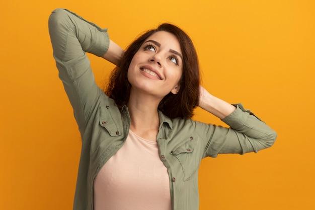 Uśmiechający się patrząc młoda piękna dziewczyna ubrana w oliwkową koszulkę trzymając się za ręce za głowę na białym tle na żółtej ścianie