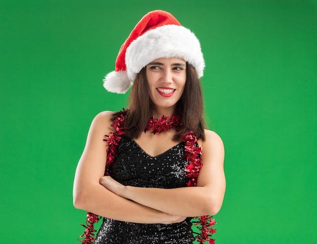 Uśmiechający się patrząc na bok młoda piękna dziewczyna ubrana w świąteczny kapelusz z girlandą na szyi skrzyżowanymi rękami na białym tle na zielonej ścianie