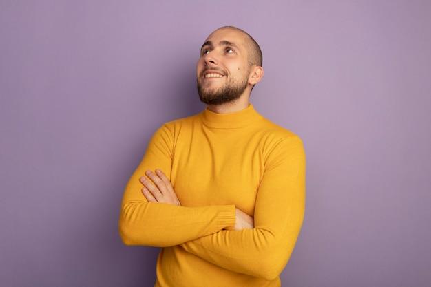 Uśmiechający się patrząc na bok młody przystojny facet skrzyżowaniu rąk na białym tle na fioletowy z miejsca na kopię