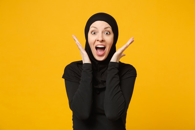 Uśmiechający się pewnie piękna młoda arabska muzułmańska kobieta w hidżab czarne ubrania pozowanie na białym tle na żółtej ścianie, portret. koncepcja życia religijnego islamu ludzi.