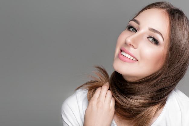 Uśmiechający się piękna brunetka kobieta z lśniące proste długie włosy. kopiuj przestrzeń