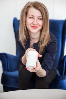 Uśmiechający się piękna kobieta patrzy na aparat i trzymając w ręku lekarstwo, używając go dla zdrowia i urody.