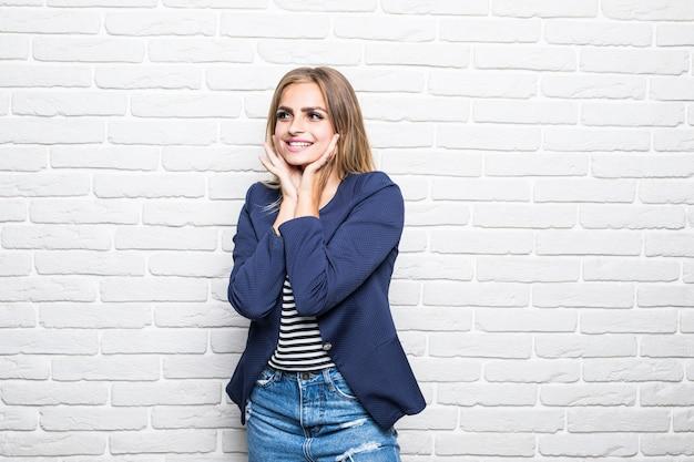 Uśmiechający się piękna kobieta stojąc na białym murem na ścianie