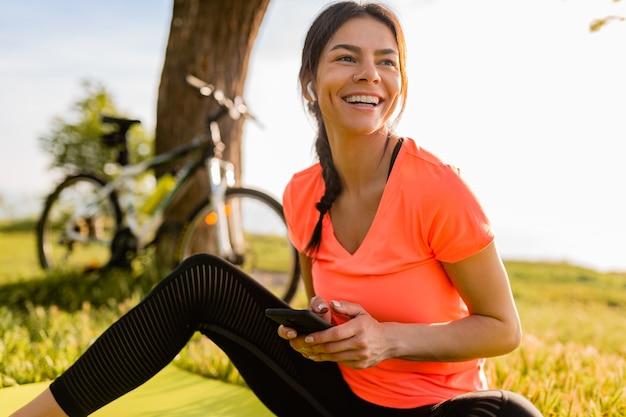 Uśmiechający się piękna kobieta trzymając telefon uprawiania sportu rano w parku