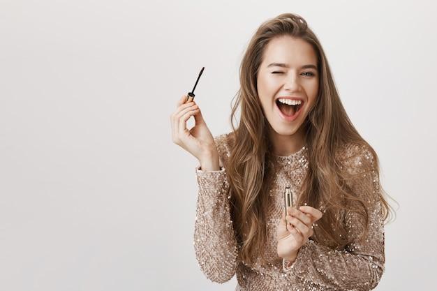 Uśmiechający się piękna kobieta za pomocą tuszu do rzęs