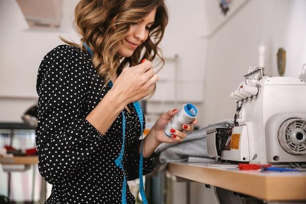 Uśmiechający się piękna krawcowa kobieta pracuje w warsztacie, przy użyciu maszyny do szycia
